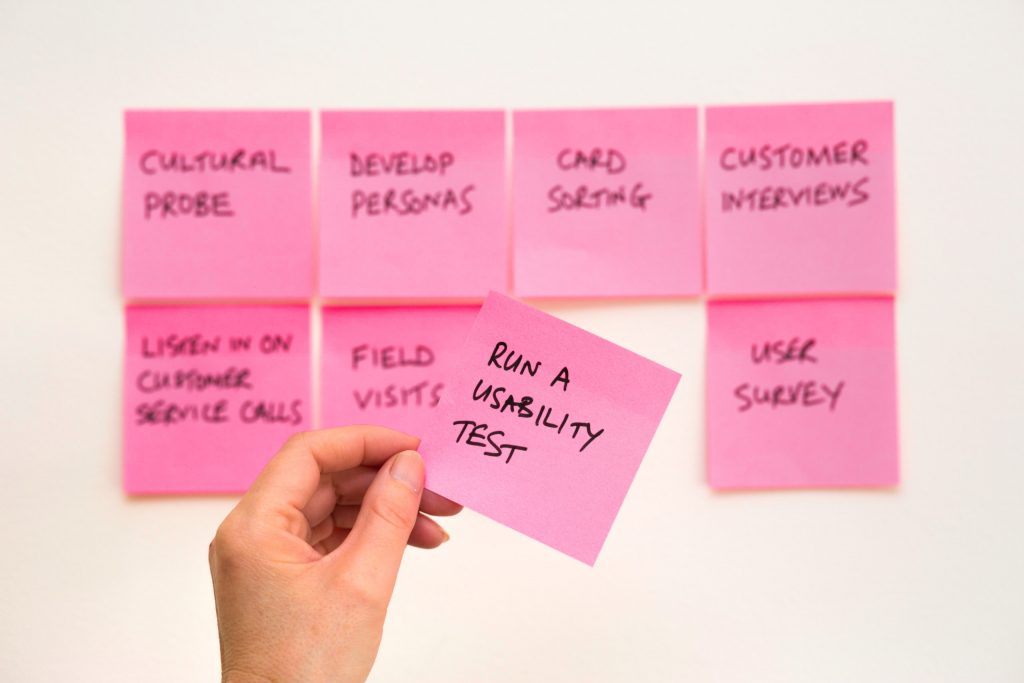 "A hand takes a sticky note with ""Run a usability test"" written on it"
